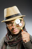 Funny detective with smoking pipe. And magnifying glass royalty free stock photo