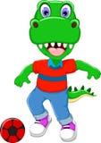 Funny dinosaur cartoon playing football Royalty Free Stock Image