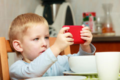Funny dirty boy child kid taking photo with red mobile phone indoor stock image