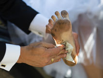 Funny dirty foot. Hand of groom with cloth, who wipes dirty foot of his bride Stock Images