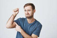 Funny dissatisfied bearded guy wearing casual clothes raising arm with pumped fist, tensing muscles to show his biceps. Funny dissatisfied bearded guy wearing Stock Photos