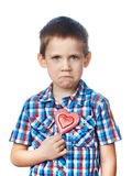 Funny dissatisfied boy with lollipop hearts Royalty Free Stock Photos