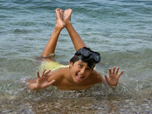 Funny diver. Boy in the sea with funny facial expression. Teen with diving mask to lie down in the shallow sea and doing funny faces (tongue sticking out, eyes Stock Image