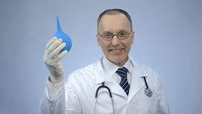 Funny doctor holding rectal syringe with smile on face, proctologist joking. Stock photo royalty free stock photos