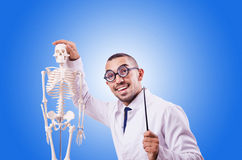 Funny doctor with skeleton against the gradient Royalty Free Stock Photos