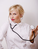 Funny doctor with stethoscope, smiling blond woman Stock Images