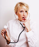 Funny doctor with stethoscope, smiling blond woman medical equipment showing on white background Royalty Free Stock Photo