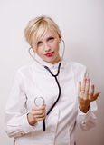 Funny doctor with stethoscope, smiling blond woman medical equipment showing on white background Stock Image