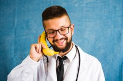 Funny doctor using banana as a phone Stock Photos