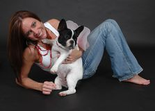 Funny Dog. Woman laying on her elbow holding her French bull dog against a black background. Dog wearing fairy wings Royalty Free Stock Photos
