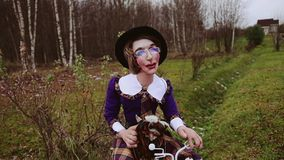 A funny doll in the form of a woman sits on a bicycle. A doll with glasses. Funny and fun doll of a woman, sitting on a bicycle. A funny parody. The doll is stock footage