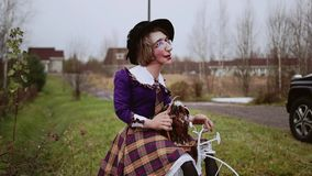 A funny doll in the form of a woman sits on a white bicycle. The middle plan. Funny and fun doll of a woman, sitting on a bicycle. A funny parody. The doll is stock video footage