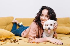 Funny domestic moments of happy young woman chilling on couch at home with domestic pet. Having fun, golden tinsels. Smiling, cheerful mood, amazing, true stock image