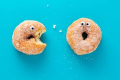 Funny doughnuts with eyes, cartoon like characters, on blue background.  stock photo
