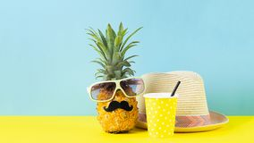 Funny dressed pineapple in glasses with black mustache, straw hat a glass with a drink a bright yellow blue background. stock images