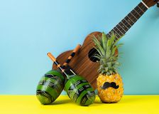 Funny dressed-up pineapple with black mustache, ukulele maracas blue yellow background. The concept holiday music party. stock image