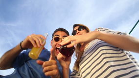 Funny drunk couple looking down at camera, drinking cocktails and laughing stock footage