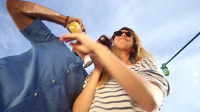 Funny drunk couple looking down at camera, toasting and drinking cocktails stock footage