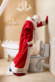Funny drunk Santa Claus peeing in the toilet. Funny drunk Santa Claus in red costume peeing in the toilet. Father Christmas alcoholic Stock Image