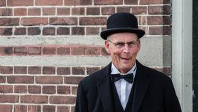 Funny dutch man with black bowler hat and glasses posing on brick wall background royalty free stock images