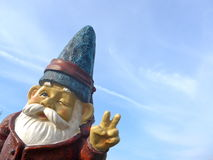 Funny dwarf with a red jacket and blue hat makes peace sign Royalty Free Stock Images