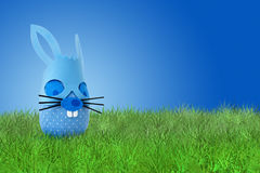 Funny Easter blue bunny on grass. Funny easter blue bunnyon grass on blue background Stock Image