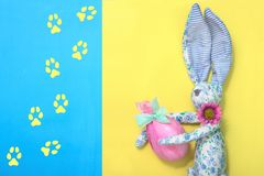 A funny Easter bunny from blue fabric in a flower holds an Easter egg in his hands is wrapped in gift pink paper and green ribbon. Royalty Free Stock Photo