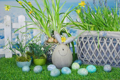 Funny easter bunny in garden. Funny easter bunny on grass with easter eggs and flower basket decorations with a white fence in background Royalty Free Stock Photo