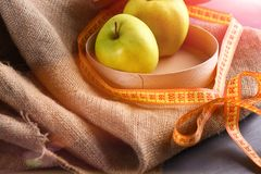Apples in wooden box on sackcloth napkin with measuring tap royalty free stock photos