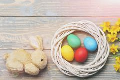 Rabbit toy, colorful easter eggs in wreath with yellow narcissus. Funny easter egg rabbit or hare toy, colorful painted easter eggs in white wreath, spring royalty free stock image