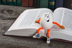 Funny Easter egg sitting on a book Stock Image