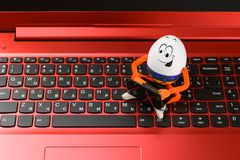 Funny Easter egg working on a red notebook computer Stock Image