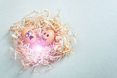 Funny Easter eggs with drawn faces depicting various emotions lying in nest Stock Photo