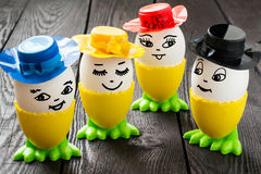 Funny Easter eggs. With a smile on the face in colorful hats on a dark wooden table Royalty Free Stock Image