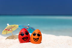 Funny easter eggs on a tropical beach. Funny easter eggs with umbrellas on a tropical beach Stock Image