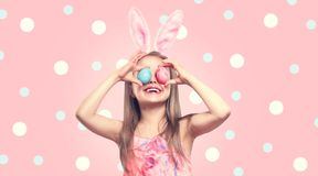 Funny Easter smiling little girl wearing bunny rabbit ears, holding colorful painted Easter eggs on her eyes. Baby girl laughing stock photos