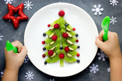 Funny edible Christmas tree for kids breakfast or dessert. Chris. Tmas treats for children. Baby eating Christmas food composition top view Stock Image