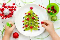 Funny edible Christmas tree for kids breakfast or dessert. Chris. Tmas treats for children. Baby eating Christmas food composition top view Stock Photography