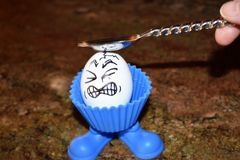 Funny egg with a painful expression as he is hit on the head with a spoon. Funny egg in a blue egg cup with a painful expression drawn on as a face as he is stock photography