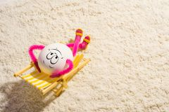Funny egg lying on a deck chaise lounge. Happy funny egg lying on a deck chaise lounge the sea. Vacation and travel concept. Copy space stock photography
