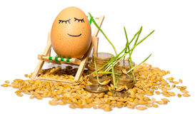 Funny egg and Stack of coins and rice seeds Stock Photos