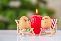 Funny eggs on a beach chair relaxing stock images
