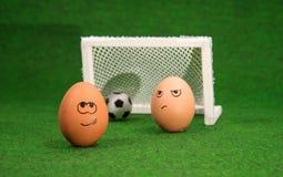 Funny eggs and football Stock Photos