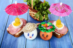 Funny eggs in the hat and wreath. With sandwiches and umbrellas. Royalty Free Stock Photo