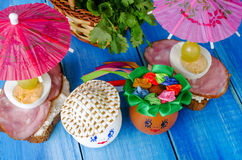 Funny eggs in the hat and wreath. With sandwiches and umbrellas. Royalty Free Stock Photography