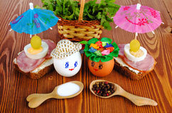 Funny eggs in the hat and wreath. With sandwiches and umbrellas. Royalty Free Stock Photos