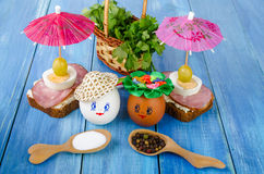 Funny eggs in the hat and wreath. With sandwiches and umbrellas. Royalty Free Stock Images