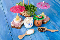 Funny eggs in the hat and wreath. With sandwiches and umbrellas. Stock Photos