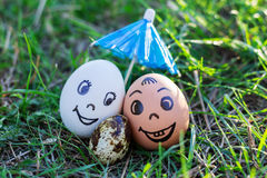Funny eggs imitate smiling mixed couple with versicolored baby Stock Photos