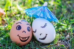 Funny eggs imitating happy mixed couple under umbrella Royalty Free Stock Images